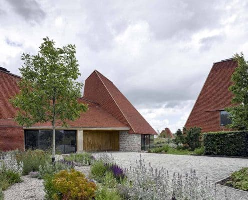 Caring Wood inner courtyard surrounded by oast style houses with handmade roof tiles in classic clay